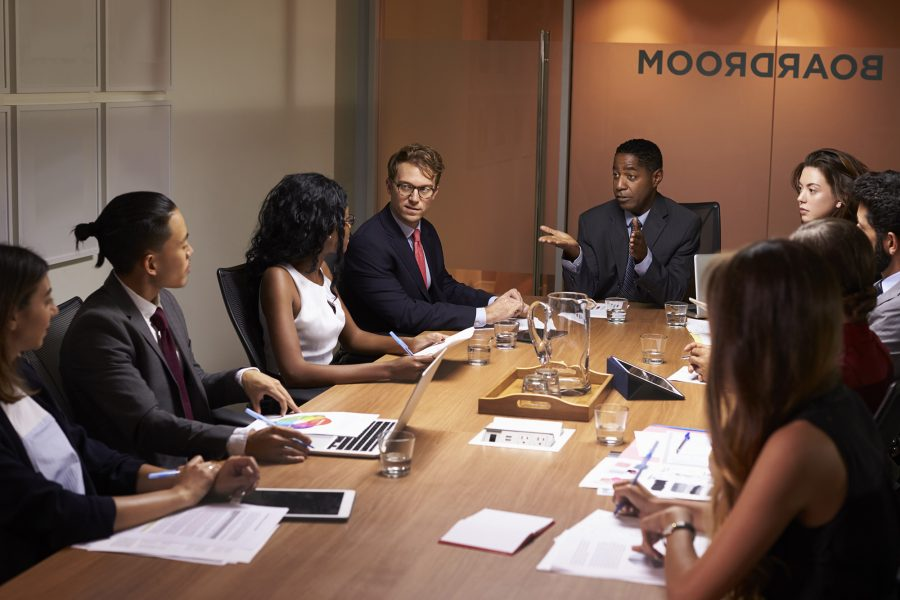 Business man addressing corporate colleagues at a meeting around a boardroom table.