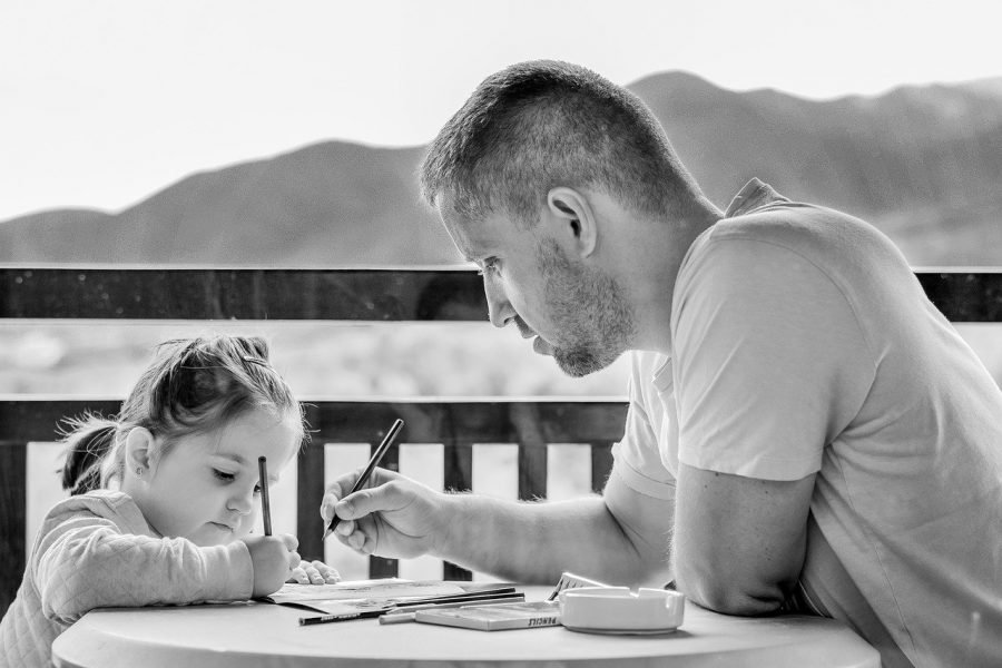 A black and white photo of a father and very young daughter doing some colouring.