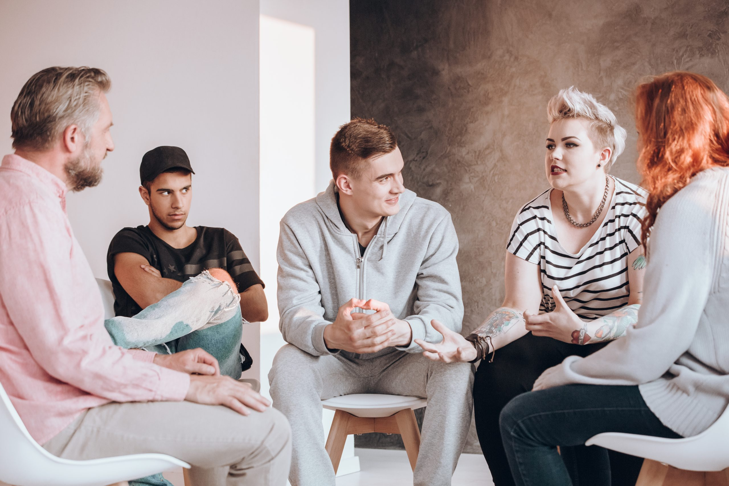 A woman expressing her opinion to a group of 3 other men and another woman. They all look quite engaged.