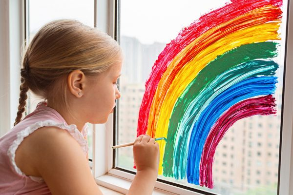 A young girl painting a rainbow on a window