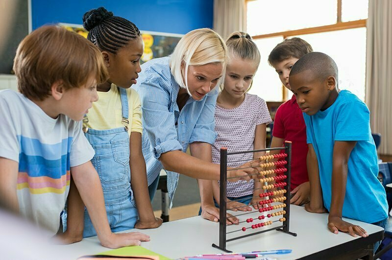 Teacher teaching a group of children maths on abacus.