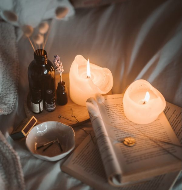 A photo of candles, books and essential oils